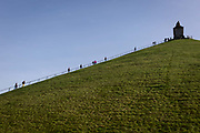 Visitors climb and descend the 225 steps, 43 metre high Waterloo Lions battlefield Mound, on 25th March 2017, at Waterloo, Belgium. The Lions Mound Butte du Lion is a large conical artificial hill completed in 1826. It commemorates the location on the battlefield of Waterloo where a musket ball hit the shoulder of William II of the Netherlands the Prince of Orange and knocked him from his horse during the battle. From the summit, the hill offers a 360 degree vista of the battlefield. The Battle of Waterloo was fought 18 June 1815. A French army under Napoleon Bonaparte was defeated by two of the armies of the Seventh Coalition: an Anglo-led Allied army under the command of the Duke of Wellington, and a Prussian army under the command of Gebhard Leberecht von Blücher, resulting in 41,000 casualties.