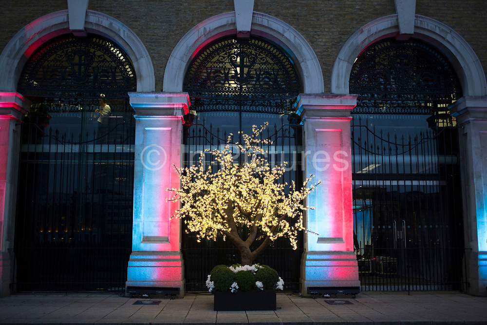 Tree lit up with fairy lights outside the old Billingsgate fish market in London, UK.