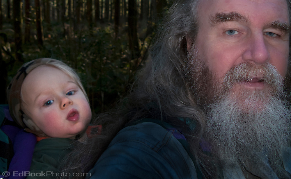 Toddler, Talus, rides on Grandpa's back on a walk in the woods.