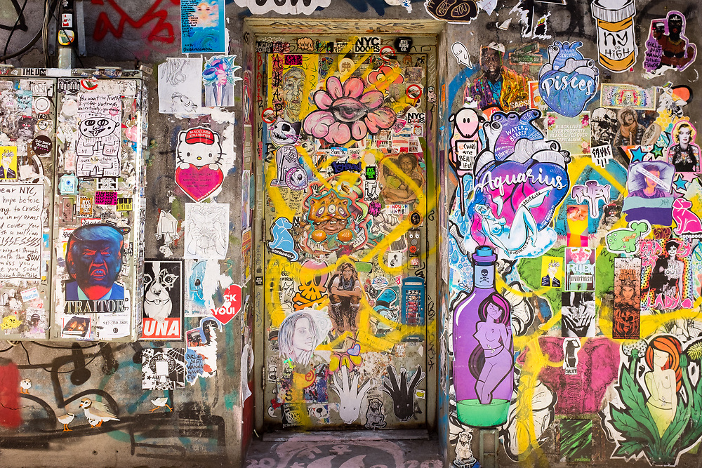 """Freeman Alley, the Bowery, New York City. Tags and wheat-pasted posters surround a doorway. On the left is a blue-faced Donald Trump poster, labelled """"traitor."""""""