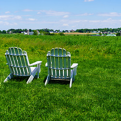 Two inviting chairs at the edge of a pasture overlooking farmland in rural Lancaster County.