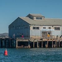 Warehouses line the docks at the harbor in Monterey, California.