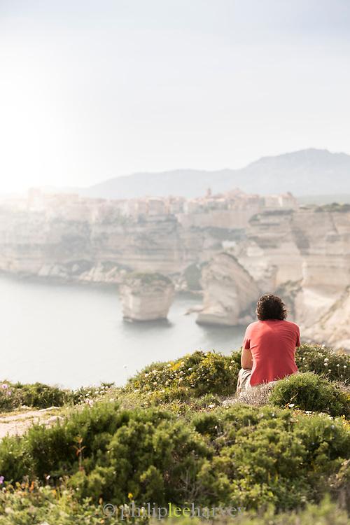 Man looking at view with limestone cliffs at sunset, Bonifacio, Corsica, France