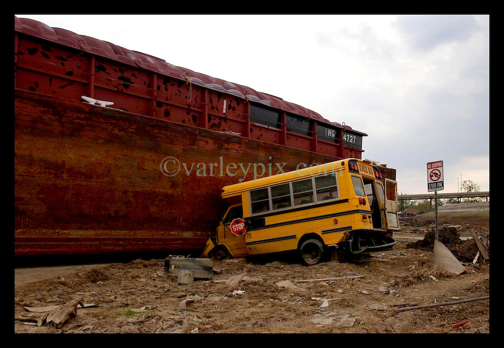 4th November, 2005.  After Katrina, New Orleans, Louisiana. Two months after Hurricane Katrina smashed the Lower 9th Ward, the floods have receded but the devastation remains. A scool bus remains trapped by a barge that washed through the levee, flooding the area.