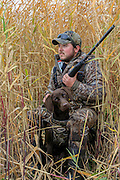 Waterfowler with his young Chocolate Lab on a Manitoba diver hunt.
