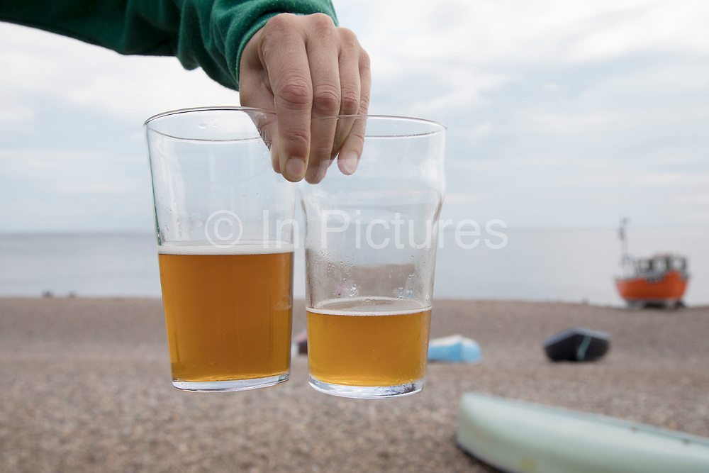 Coastal seaside view with two half full pint glasses of ale at Branscombe, Devon, England, United Kingdom. It is located within the East Devon Area of Outstanding Natural Beauty, overlooking Lyme Bay. The village straggles along narrow roads down steep-sided valleys, terminating at a shingle beach, Branscombe Mouth, which forms part of the East Devon and Dorset Jurassic Coast. To either side of the beach, the coast rises steeply to cliffs, which are in the ownership of the National Trust. It is a popular point for starting walks on the South West Coast Path.