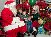 Braedyn, Ryan and Jordyn Carroll enjoy their time with Santa Claus at Heath's Supermarket in Center Harbor to ask what they would each like for Christmas this year.  (Karen Bobotas/for the Laconia Daily Sun)