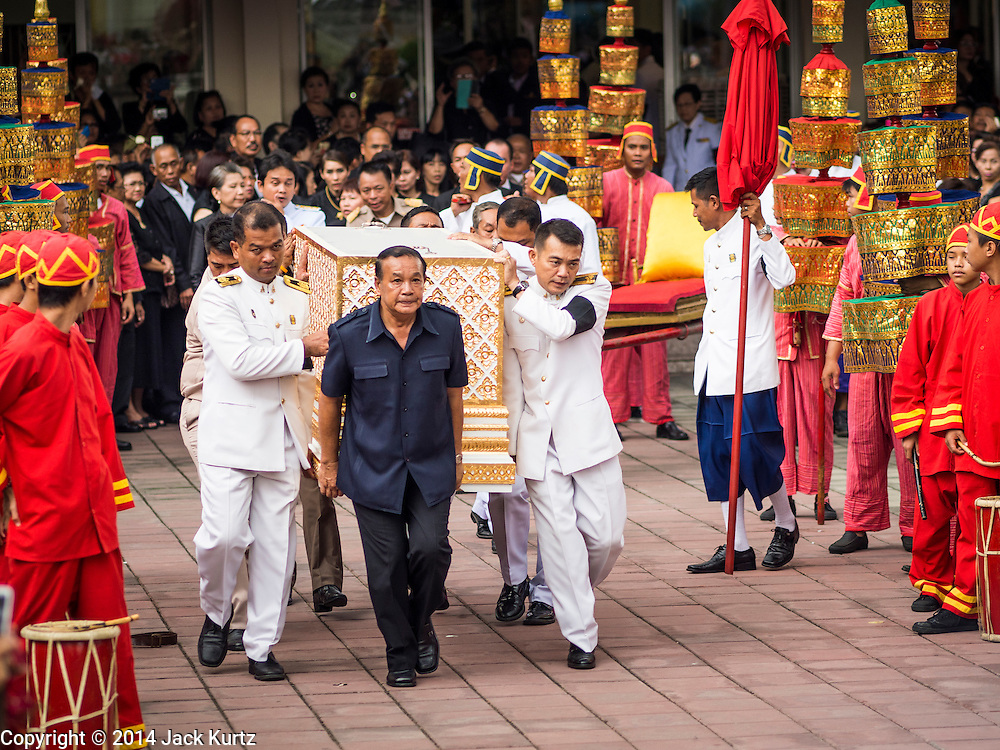 19 OCTOBER 2014 - BANG BUA THONG, NONTHABURI, THAILAND: Apiwan Wiriyachai's coffin is carried to the crematorium during his cremation at Wat Bang Phai in Bang Bua Thong, a Bangkok suburb, Sunday. Apiwan was a prominent Red Shirt leader. He was member of the Pheu Thai Party of former Prime Minister Yingluck Shinawatra, and a member of the Thai parliament and served as Yingluck's Deputy Prime Minister. The military government that deposed the elected government in May, 2014, charged Apiwan with Lese Majeste for allegedly insulting the Thai Monarchy. Rather than face the charges, Apiwan fled Thailand to the Philippines. He died of a lung infection in the Philippines on Oct. 6. The military government gave his family permission to bring him back to Thailand for the funeral. His cremation was the largest Red Shirt gathering since the coup.     PHOTO BY JACK KURTZ