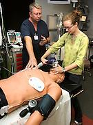 Clinical educator, John Jarred, (left), instructs pre-med student, Katherine Bakke, at the Arizona Simulation Technology and Education Center, University Medical Center, University of Arizona, Tucson, Arizona, USA.