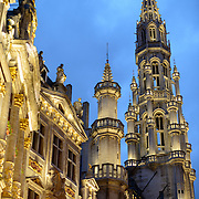 At left of frame is some of the outside of one of the guildhalls and at right the tower of the Town Hall in the Grand Place, Brussels. Originally the city's central market place, the Grand-Place is now a UNESCO World Heritage site. Ornate buildings line the square, including guildhalls, the Brussels Town Hall, and the Breadhouse, and seven cobbelstone streets feed into it.