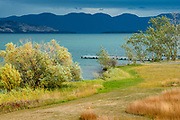 Limited Editions of 8<br /> A late summer storm moves across Flat Head Lake in Montana with dark skies in the distant and sunshine illuminating foliage and grass around a boat dock