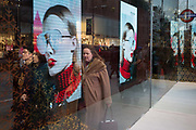 Shoppers merge with the image of a womans face modelling sunglasses in Covent Garden in central London, on 4th December 2017, in London England.