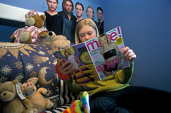 Teenage girl in her bedroom reading More magazine UK