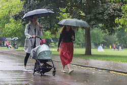 © Licensed to London News Pictures. 04/06/2021. London, UK. Members of the public walk in the rain through Victoria Park, east London. Photo credit: Marcin Nowak/LNP