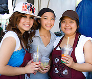 Hmong teen food concession workers enjoy their cups of fruit drink. Hmong Sports Festival McMurray Field St Paul Minnesota USA