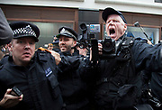London, UK. Tuesday 11th June 2013. Police photographer shouts at protesters to stand back during a demonstration against the upcoming G8 summit in central London, UK.