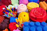 Silicone cake moulds in bright colours on sale at the market in Pienza, Tuscany, Italy