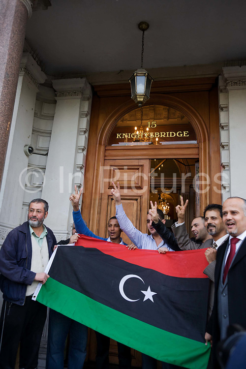 Libyan nationals and diplomatic staff celebrate with their the revolutionary flag on the steps outside their London embassy in Knightsbridge, central London on 20/10/11, reacting to the death earlier in Sirte of the dictator Muammar Muhammad Abu Minyar al-Gaddafi, on the day his 42 year rule over Libya came to an official end.