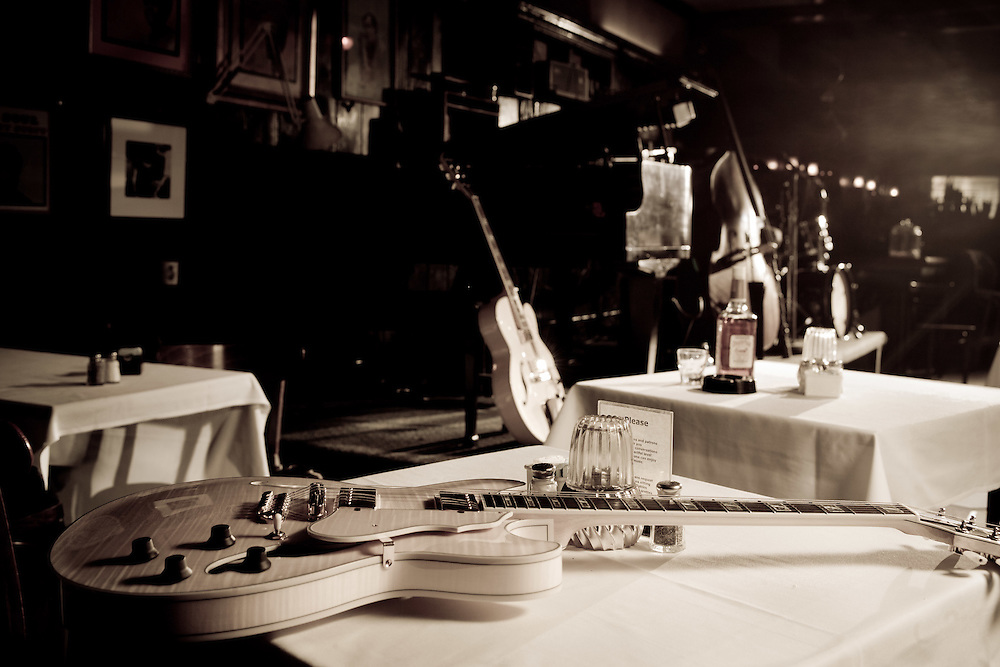 This picture of Ortliebs's  an empty jazz and blues club or bar was taken in the Casablace or Film Noir genres of pictures. The stage has a light colored Artcore guitar, leaned against a piano stool, piano, acoustic bass or double bass, and drum set on stage with formal white tablecloths three tables. A second Artcore lightcolored guitar lays across table in the foreground. Rose bottle of liquor next to ashtray and empty glass on one table.
