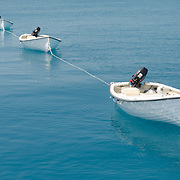 A series of five small dories strung behind a larger boat on the water of Swains Reef on Australia's Great Barrier Reef.