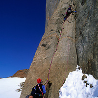 ANTARCTICA, Queen Maud Land. Conrad Anker (MR) climbs the 1st pitch on Rakekniven spire in the Filchner Mts.