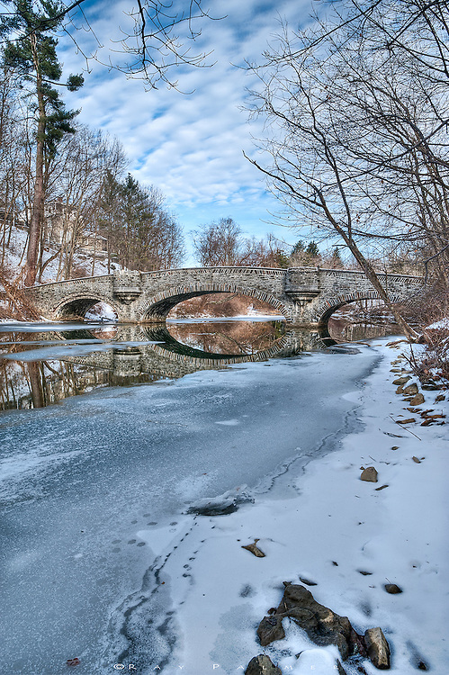 The Clark Footbridge reflects in the Susquehanna River, Cooperstown, NY