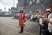 London, UK. Tuesday 23rd July 2013. Smoke drifts past as a Beefeater on guard watches over public and tourists gathering to see the 62 gun salute at the Tower of London, to mark the birth of the Duke and Duchess of Cambridge's son.