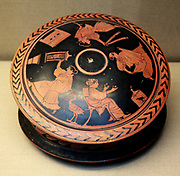 Red-figured pyxis (trinket-box) with a lid showing a woman holding a 'sprang' frame. Greek, ,made in Athens around 470 BC. This frame differs in its rectangular shape from the tapering version shown on the vase 1909.11-2.3 also exhibited in the case.