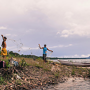 "Grandfather and his grandson fizing a fishing net in a community near Cucui, on the Brazilian side of the triple border between Brazil, Colombia and Venezuela in the Amazon. On the background,  the ""Pedra do Cucui"" a spectacular rocky formation in the Venezuelan territory"