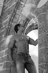 shirtless bodybuilder standing in a stone archway in Bermuda