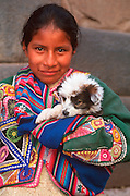 PERU, HIGHLANDS, CUZCO young Quechua Indian girl with puppy
