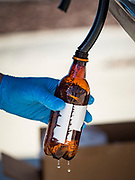 """20 MARCH 2020 - DES MOINES, IOWA: Workers at the Foundry, a distillery in Des Moines, pour hand sanitizer into a used root beer bottle for a waiting motorist. The distillery suspended its distilling operations to make hand sanitizer this week. They distributed it free to people who came to their building. On Friday thousands of people came to get some. There line was more than one mile long. On Friday morning, 20 March, Iowa reported 45 confirmed cases of the Coronavirus. Restaurants, bars, movie theaters, places that draw crowds are closed for at least 30 days. There are no """"shelter in place"""" orders in effect anywhere in Iowa but people are being encouraged to practice """"social distancing"""" and many businesses are requiring or encouraging employees to telecommute.      PHOTO BY JACK KURTZ"""