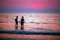 Two Hindu men wading in the waters of the Arabian Sea off Juhu Beach, Mumbai (Bombay), India
