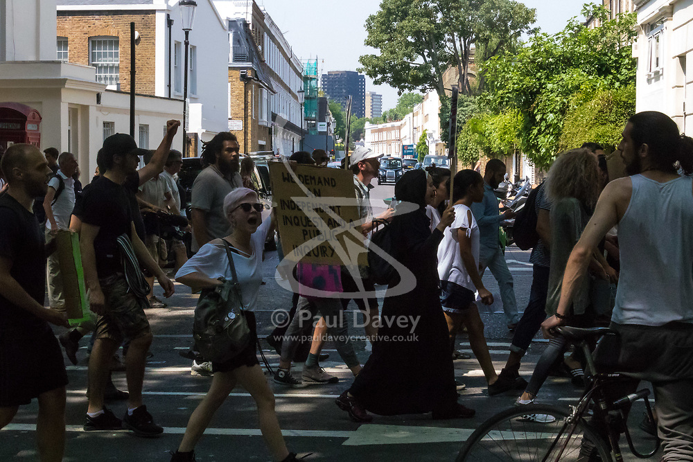 London, June 21st 2017. Protesters march through London from Sheherd's Bush Green in what the organisers call 'A Day Of Rage' in the wake of the Grenfell Tower fire disaster. The march is organised by the Movement for Justice By Any Means Necessary and coincides with the Queen's Speech at Parliament, the destination. PICTURED: With the burnt out hulk of Grenfell Tower in the distance, the crowd of several hundred marches past Holland Park.