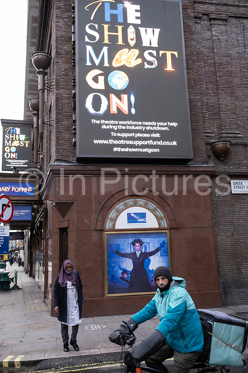 Deliveroo courier stops beside the show muct go on sign outside the closed Prince Edward Theatre in Soho which is showing Mary Poppins in the West End as the national coronavirus lockdown three continues and theatres have to remain shut on 28th January 2021 in London, United Kingdom. Following the surge in cases over the Winter including a new UK variant of Covid-19, this nationwide lockdown advises all citizens to follow the message to stay at home, protect the NHS and save lives.