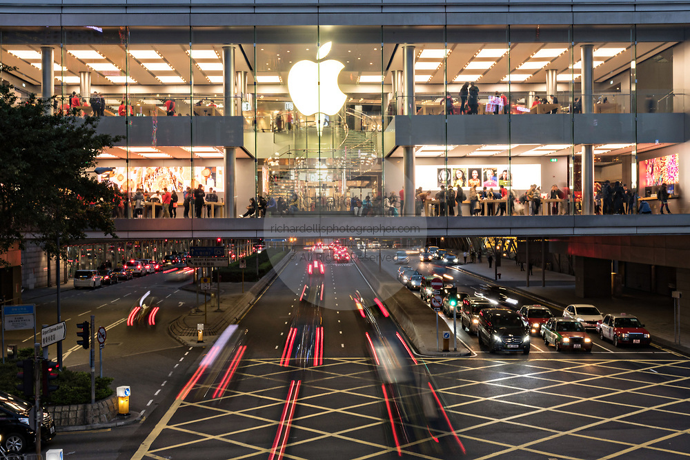 Traffic passes under the Apple flagship store at the IFC Mall on Lung Wo Road in the Central District of Hong Kong.