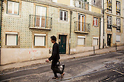 Young man passes in front of a facade decorated with ceramic tiles in Alfama district, in Lisbon.