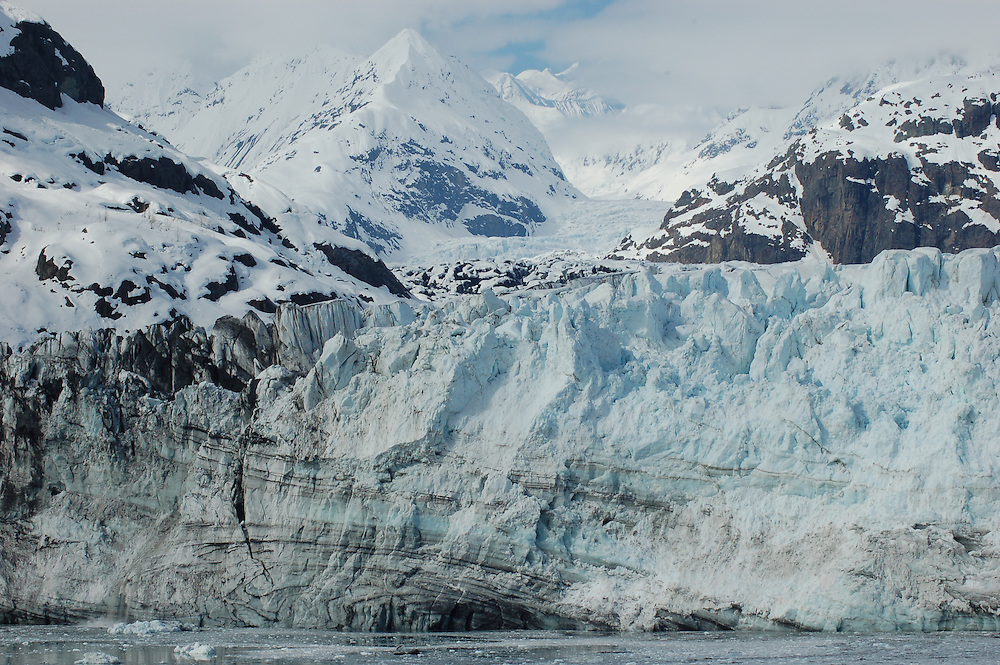 This is a glacier emerging from a mountain range along the coast of Alaska.