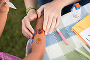 Helen Lai (4) receives several temporary tattoos during National Night Out at Berryessa Creek Park in San Jose, Calif., on Aug. 7, 2012.  Kids of all ages enjoyed face painting, various games, ice cream, and an outdoor viewing of Disney's Up.  Photo by Stan Olszewski/SOSKIphoto.