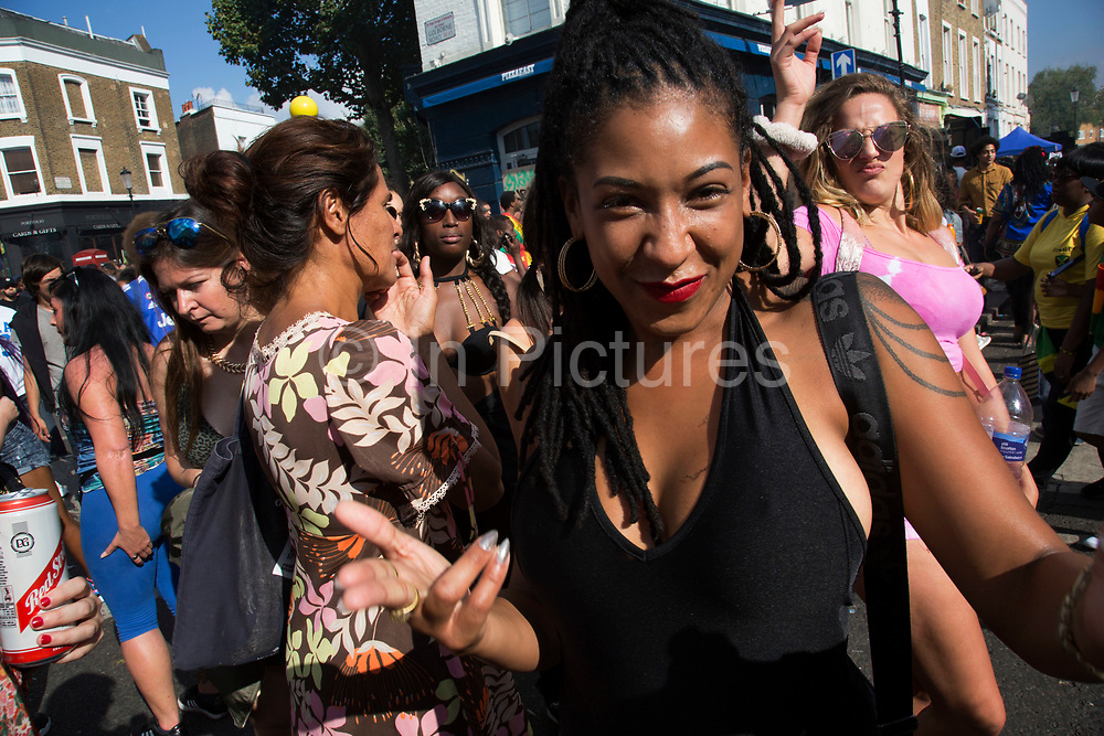 Crowd gathers on Golborne Road on Monday 28th August 2016 at the 50th Notting Hill Carnival in West London. A celebration of West Indian / Caribbean culture and Europes largest street party, festival and parade. Revellers come in their hundreds of thousands to have fun, dance, drink and let go in the brilliant atmosphere. It is led by members of the West Indian / Caribbean community, particularly the Trinidadian and Tobagonian British population, many of whom have lived in the area since the 1950s. The carnival has attracted up to 2 million people in the past and centres around a parade of floats, dancers and sound systems.