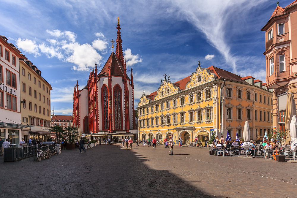 The market square in Würzburg, Germany. Cafes as well as Mary's Chapel, a Gothic church, surround the heart of the city. The yellow Falcon House is a beautiful, patrician house facing the square.