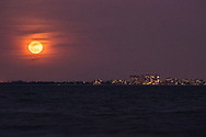 A full red moon rises above the large condos that line the horizon's edge across Fort Myers Beach in Florida.
