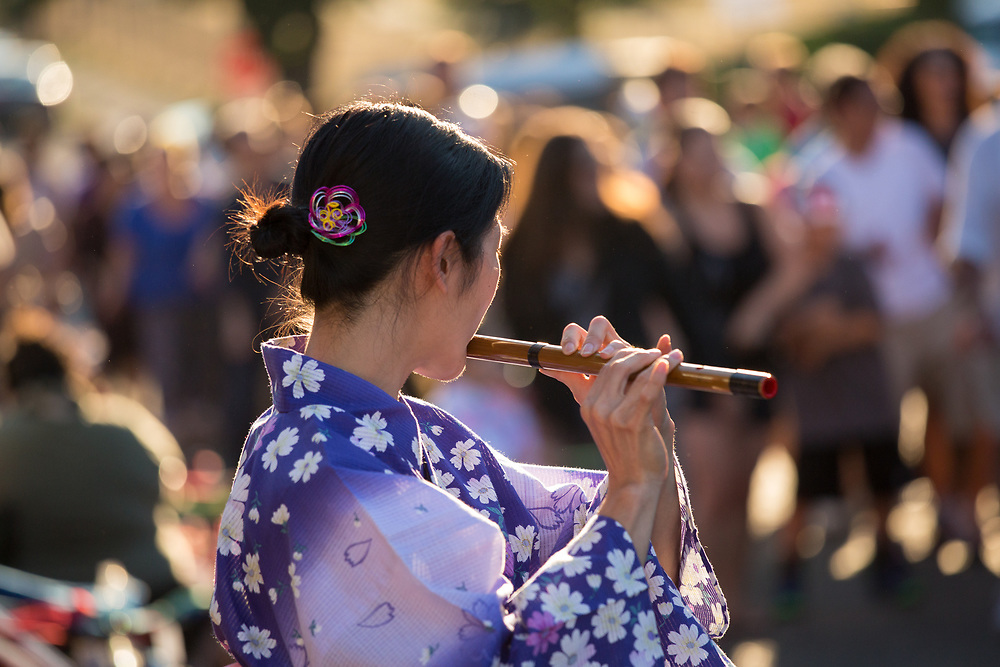 "United States, Washington, Seattle. Chinese New Year celebration in Seattle's ""International District"", traditional home of the city's Asian community. Woman playing flute."