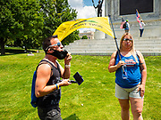 04 JULY 2020 - DES MOINES, IOWA: A member of Black Lives Matter (left) argues with a Donald Trump supporter on the grounds of the Iowa State Capitol. Hundreds of people came to the grounds of the Iowa State Capitol to protest against and in favor of historic monuments on the capitol grounds. Several hundred people protested against a monument to Christopher Columbus and the stereotypical depiction of Native Americans on the capitol grounds. About 50 people came to the capitol to rally in support of the monuments. The protest against the monuments was organized by Seeding Sovereignty, a collective of indigenous women. The rally to defend the monuments was organized by an Iowa chapter of Three Percenters.     PHOTO BY JACK KURTZ