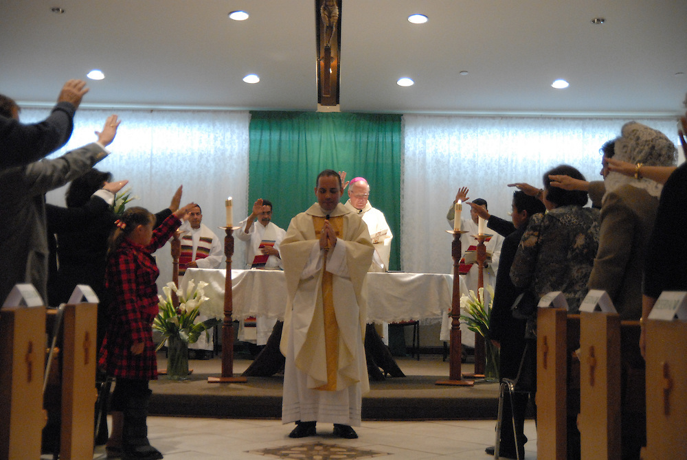 Bishop George Rassas (center rear) leads parishioners in prayer while installing Fr. Claudio Diaz (C) as Pastor of Mision San Juan Diego in Arlington Heights.