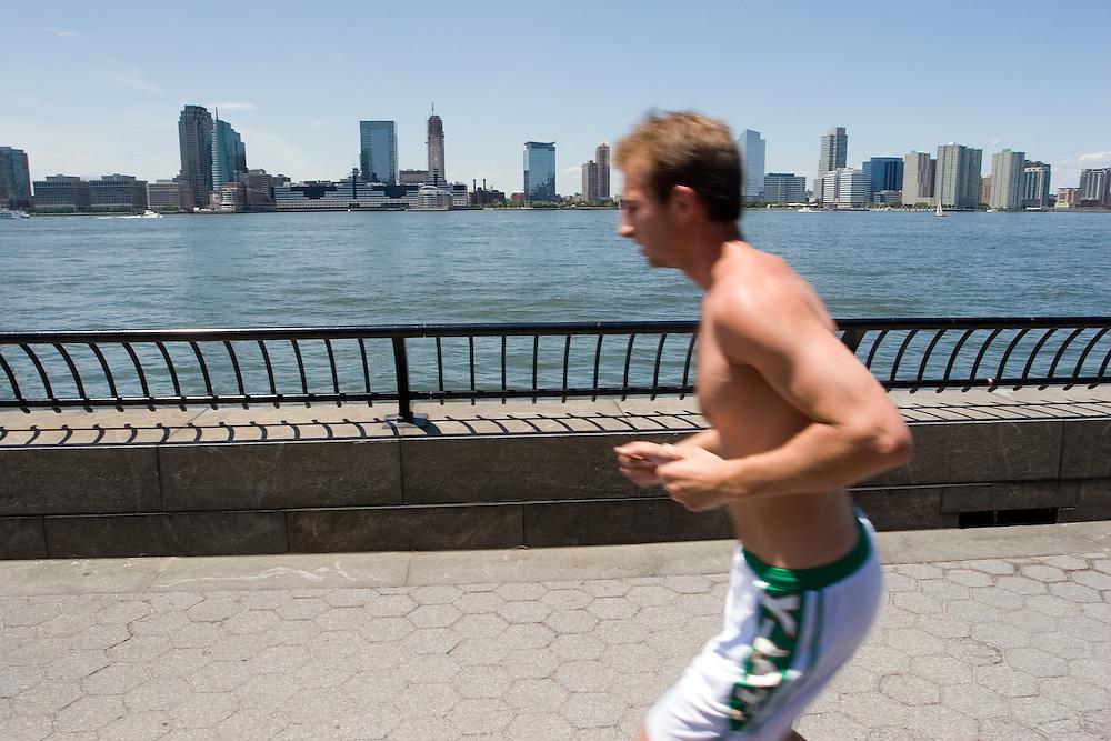 A Newyorker jogging by Hudson River close to Governor Nelson Rockefeller Park. Jersey City in the background.<br /> Un joven neoyorkino hace deporte junto al el río Hudson cerca del Governor Nelson Rockefeller Park, con los edificios de Jersey City al fondo.