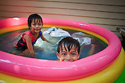 """Mar 23, 2009 -- BANGKOK, THAILAND: Children play in an inflatable pool in front of their home in Ban Krua. The Ban Krua neighborhood of Bangkok is the oldest Muslim community in Bangkok. Ban Krua was originally settled by Cham Muslims from Cambodia and Vietnam who fought on the side of the Thai King Rama I. They were given a royal grant of land east of what was then the Thai capitol at the end of the 18th century in return for their military service. The Cham Muslims were originally weavers and what is known as """"Thai Silk"""" was developed by the people in Ban Krua. Several families in the neighborhood still weave in their homes.     Photo by Jack Kurtz"""