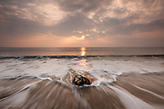 A lobster pot is washed ashore by slow powerful waves at sunset at Dinas Dinlle beach near Caernarfon, North Wales.