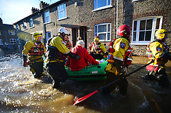 © Licensed to London News Pictures. 27/12/2015. York, UK.  A mountain rescue team evacuate an elderly resident from a flooded street in York City centre. Large areas of the North of England have been hit by severe flooding following unusually heavy rainfall in December. Photo credit: Ben Cawthra/LNP