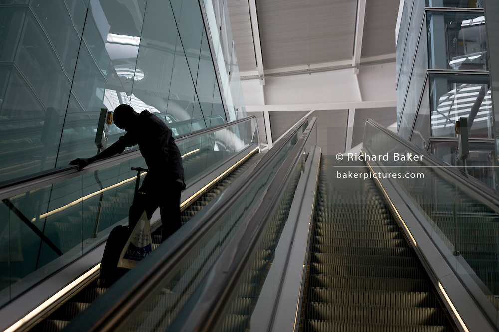 A lone departing passenger descends one of the 105 escalators in Terminal 5 of London's Heathrow Airport. .